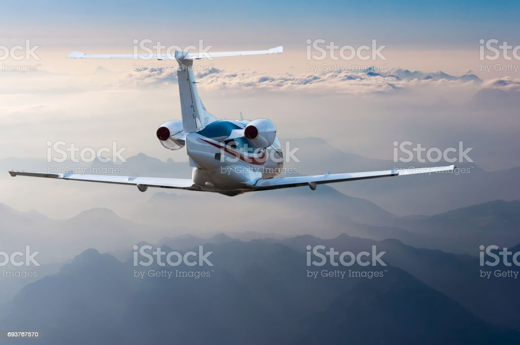 Private jet, passenger wide-body plane or aircraft is flying in the blue sky over the the clouds and mountains. Summer vacation concept stock photo