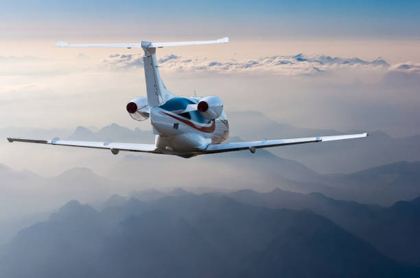 Privat-Jet, Widebody-Passagierflugzeug oder Flugzeug fliegt in den blauen Himmel über den Wolken und Berge. Sommer Urlaub Konzept – Foto