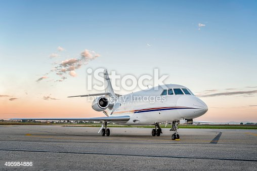 Wide angle view of private luxury business jet parked at the airport asphalt runway, no people image of air vehicle, space for copy. Beautiful blue sky with dusk.