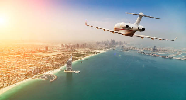 Private jet plane flying above Dubai city in beautiful sunset light. Private jet plane flying above Dubai city in beautiful sunset light. Modern and fastest mode of transportation, business life. military private stock pictures, royalty-free photos & images