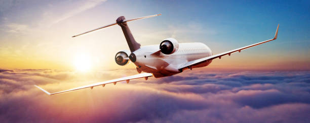Private jet plane flying in sunset stock photo