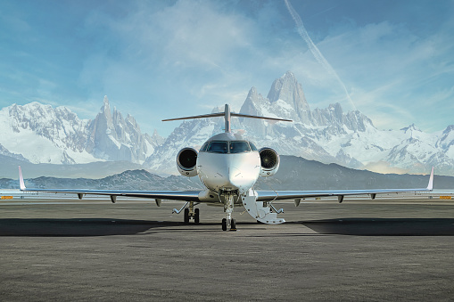 Head on photo of a private jet waiting on runway to be boarded with snowy mountains in the background