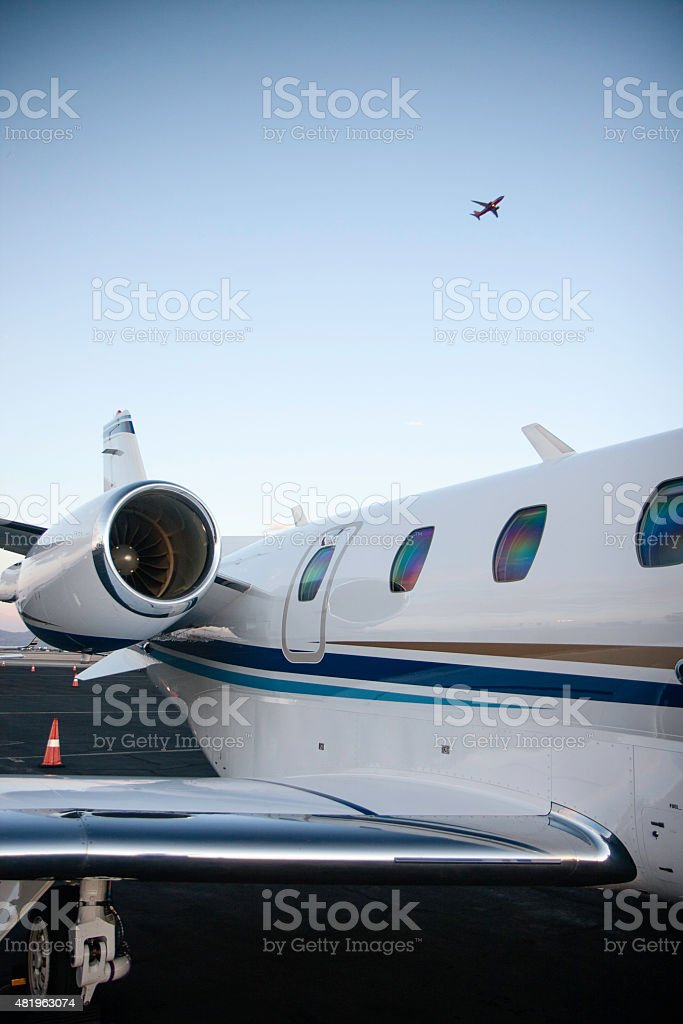 Private Jet with Airline Overhead stock photo