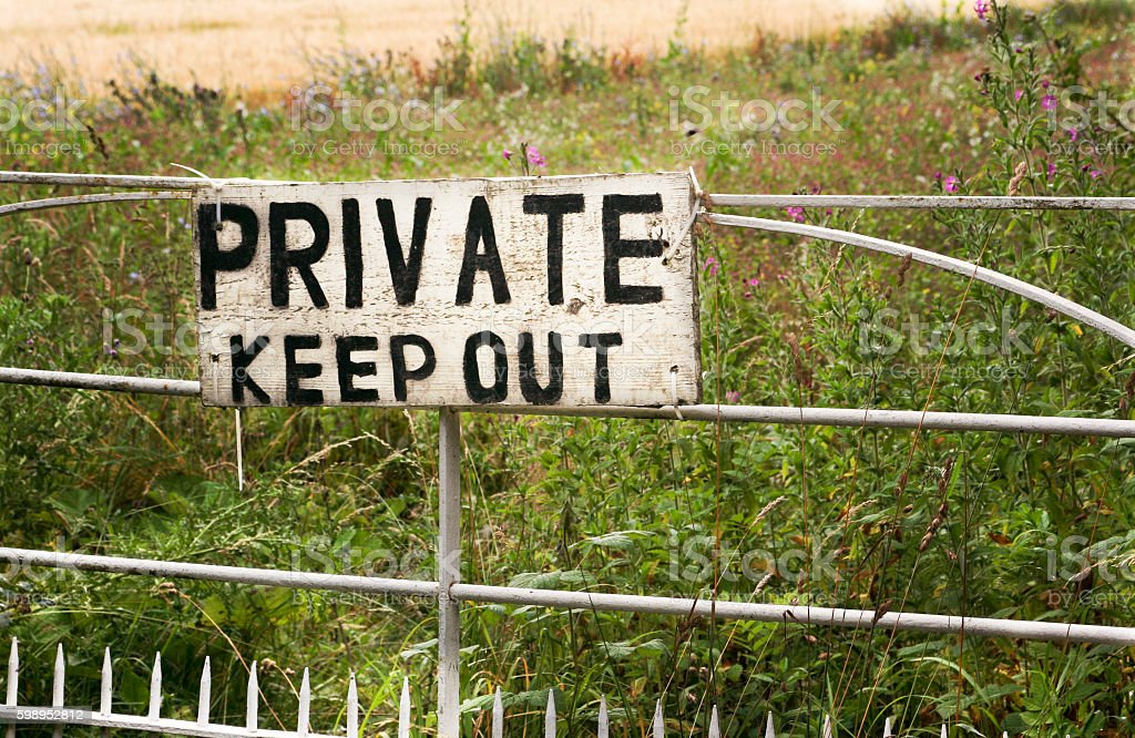 Private, Keep Out Weathered private keep out sign on fence in field Agricultural Field Stock Photo