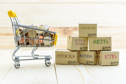 1155852718 istock photo Private portfolio and wealth management with risk diversification concept : Paper boxes of financial instruments i.e ETFs, REITs, stocks, bonds, mutual funds, commodities and shopping cart with coins. 1036559114