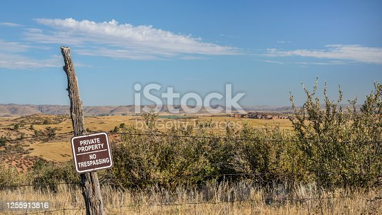 private property, no trespassing sign on barbed wire fence at Colorado foothills, fall scenery
