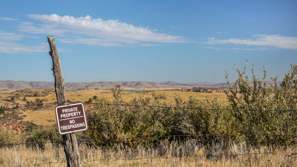 private property, no trespassing sign on barbed wire fence stock photo