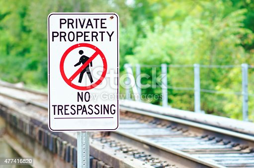 Sign by railroad tracks warning people to stay off the private property.