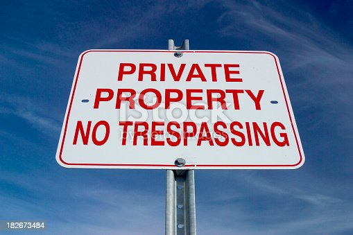 Sign depicting Private Property shot against graduated blue sky with light clouds.
