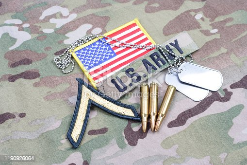 istock US ARMY Private rank patch, flag patch, with dog tag and 5.56 mm rounds on camouflage uniform 1190926064