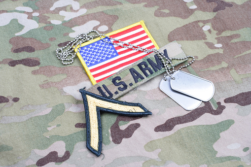 istock US ARMY Private rank patch, flag patch, with dog tag on camouflage uniform 1190926196
