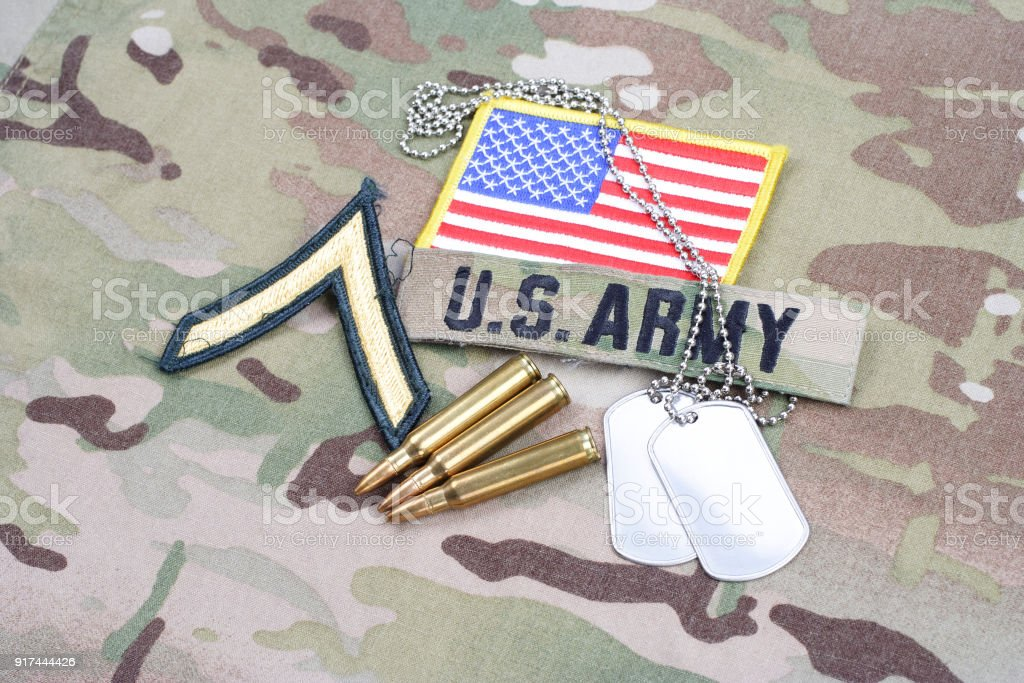 US ARMY Private rank patch, flag patch, with dog tag with 5.56 mm rounds on camouflage uniform stock photo