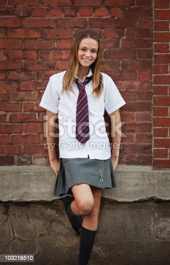 istock Private school girl, standing against a brick wall 103216510