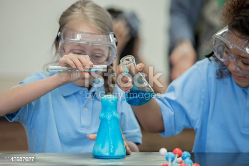 istock Private school student with Down Syndrome does chemistry experiment with friend in laboratory 1142687627