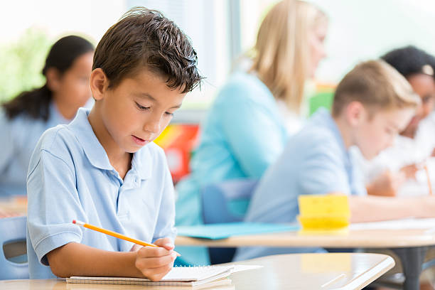 private school student writes something in class - private school stock photos and pictures