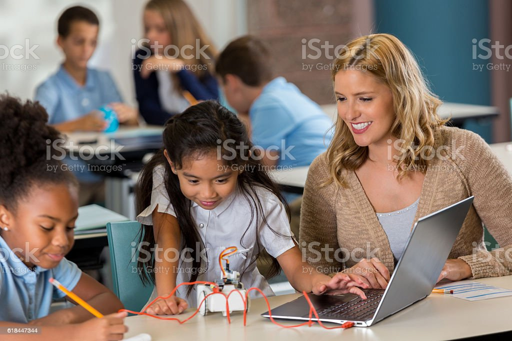 Private STEM school students work on class assignment Diverse STEM private schoolgirls concentrate while working on a project in technology class. Their mid adult Caucasian teacher is helping them. Adult Stock Photo
