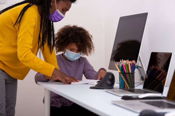 A private teacher woman helping 6 years old school child to read. Both are wearing face masks, reading, studying, using an exercise book, pencils, computers, and the internet. Coronavirus pandemic education concept. stock photo