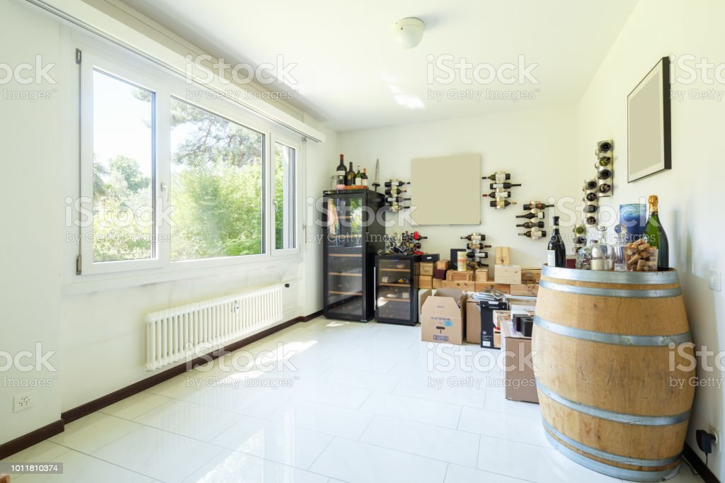 Private wine cellar with many wines, boxes and wooden barrels stock photo