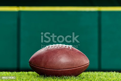Low angle view, of a textured pro American Football made of leather sitting on artificial turf of a stadium with green padded wall in the background. This type of football with the white stripes is used by the NFL.