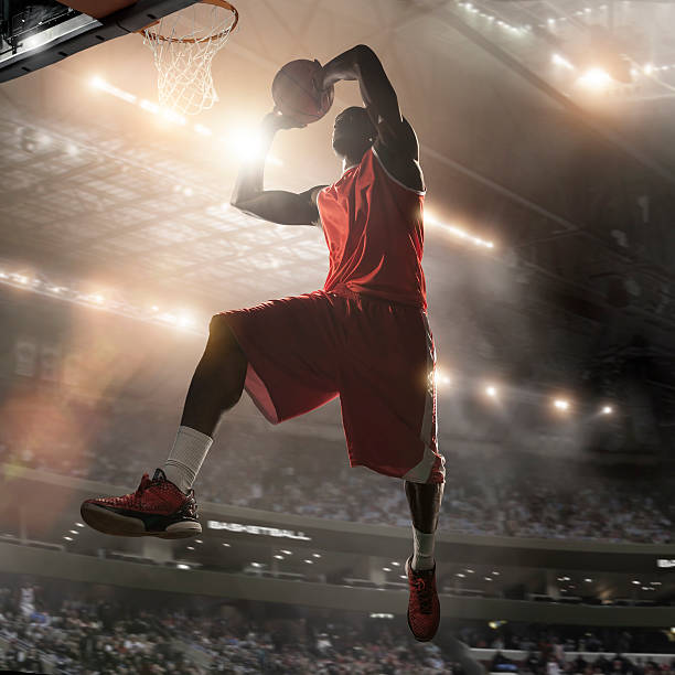 Pro Basketball Player About To Dunk Mid action image of basketball player in mid air holding basketball above head about to slam dunk in basketball hoop. Action occurs in generic indoor floodlit basketball arena full of spectators. All arena advertising is fake. Basketball player is wearing generic strip. With intentional motion blur to background and lensflare. jump shot stock pictures, royalty-free photos & images