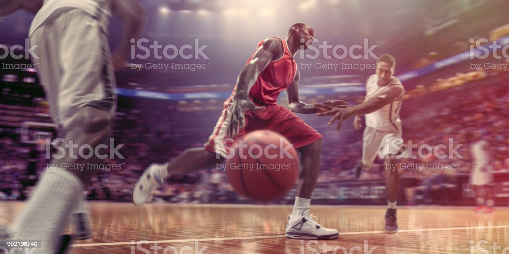 Pro Basketball Player Dribbling Ball Past Opponents During Basketball Game stock photo