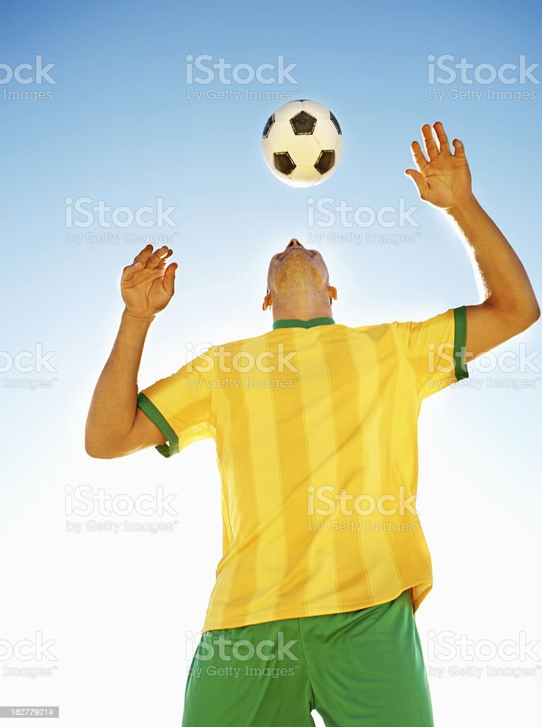 Pro football player heading the ball against clear sky royalty-free stock photo