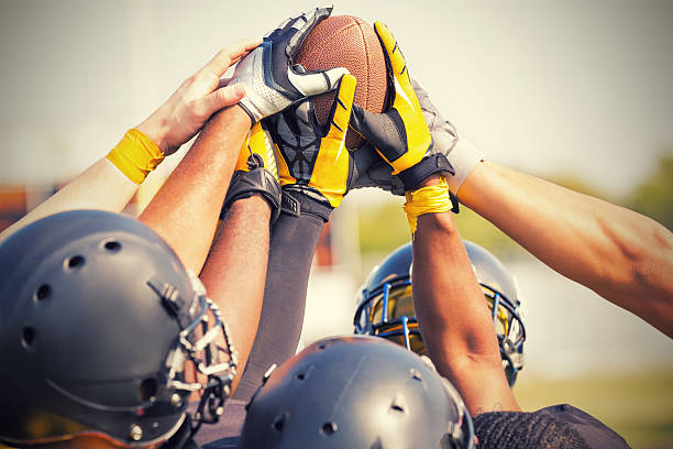 Pro football players holding ball in huddle stock photo