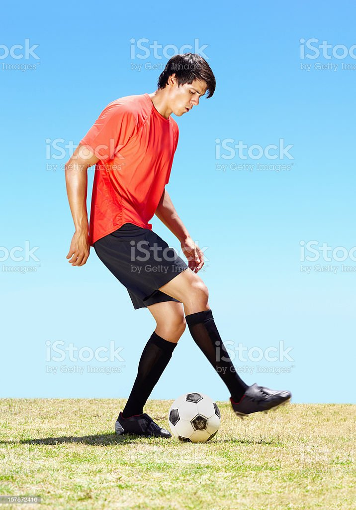 Pro footballer dribbling with a ball on the field royalty-free stock photo
