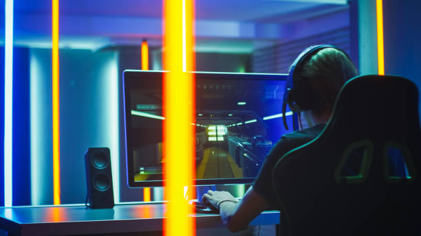 Pro Gamer Plays in the First Person Shooter on His Personal Computer. Talks with Teammates through Headphones. Neon Colored Room. Online eSport Tournament in Action. stock photo