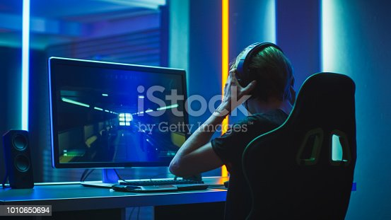 istock Pro Gamer Plays in the First Person Shooter on His Personal Computer. He Puts on His Headphones. Neon Colored Room. Online eSport Tournament in Action. Shot on Anamorphic Lens. 1010650694