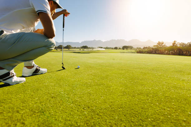 Pro golf player aiming shot with club on course stock photo