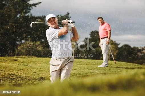 Pro golfer playing on the course with second player standing at back looking on. Man hitting the ball out of a sand bunker during the game.