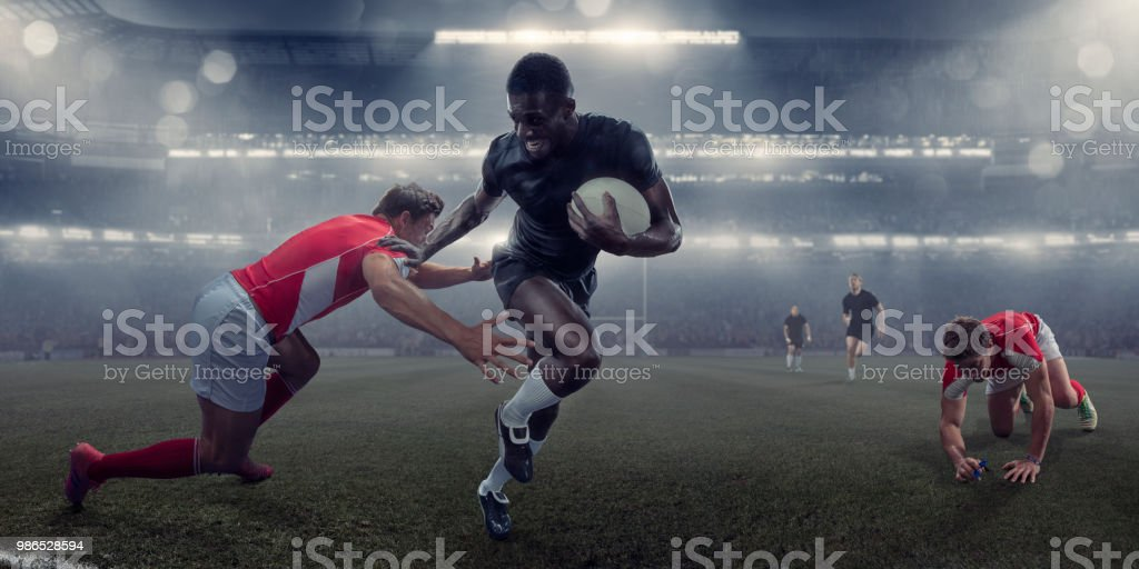 Pro Rugby Player Running With Ball Past Tackling Opponent stock photo