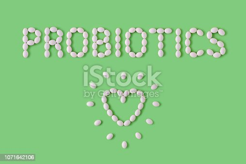 istock Probiotics word made of pills on green background. Flat lay, top view, free copy space. Natural medical pharmacy concept. Probiotics benefits. 1071642106