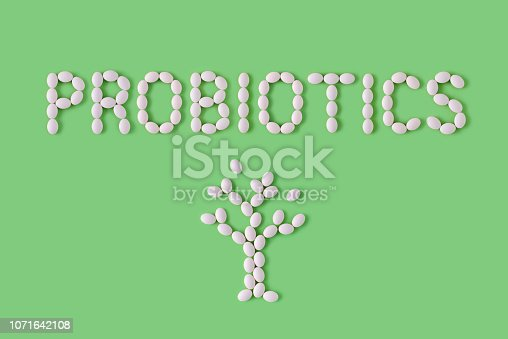 istock Probiotics word made of pills on green background. Flat lay, top view, free copy space. Natural medical pharmacy concept. Probiotics benefits. 1071642108