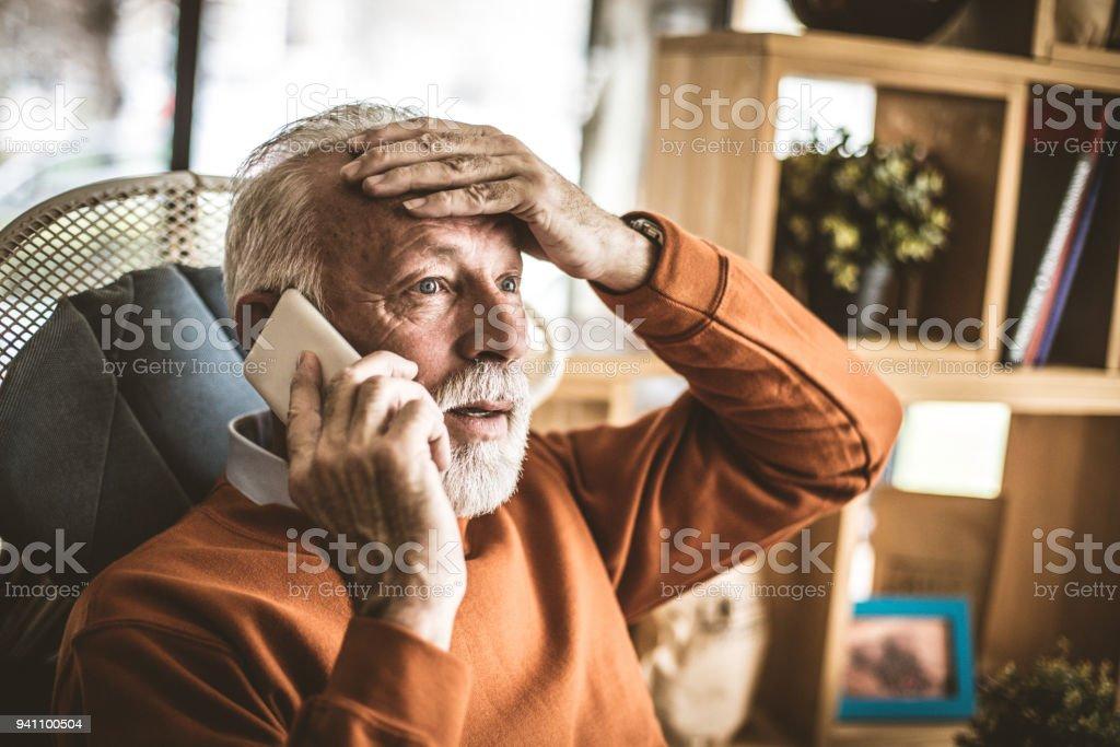 Problem at office. Senior businessman talking phone. stock photo