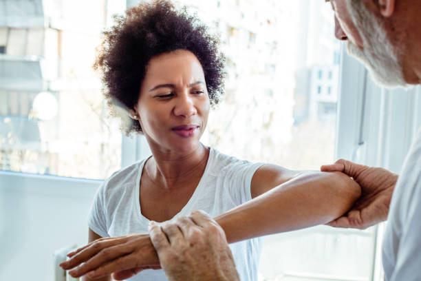 Problem is at the elbow. Problem is at the elbow. Physiotherapist working with patient. joint pain stock pictures, royalty-free photos & images