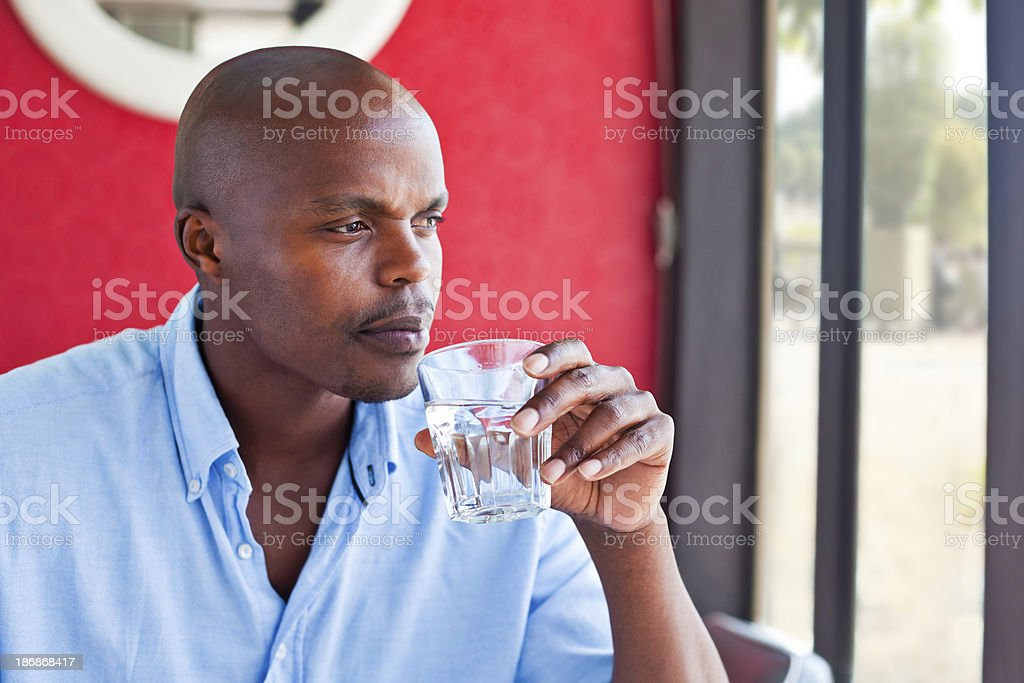 Problem A worried african man looking out the windown and drinking water. Adult Stock Photo