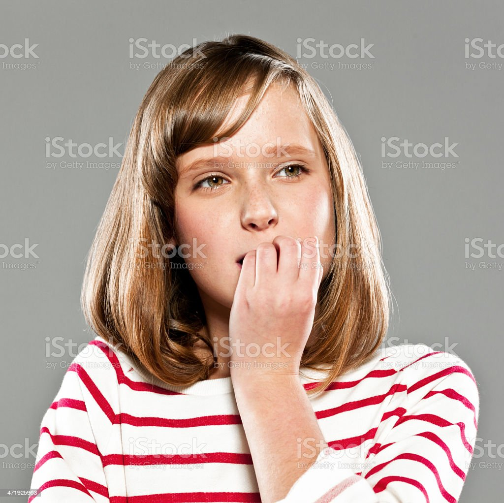 Problem Portrait of worried girl wearing striped blouse looking away and bitting her nails. Studio shot on grey background. 10-11 Years Stock Photo