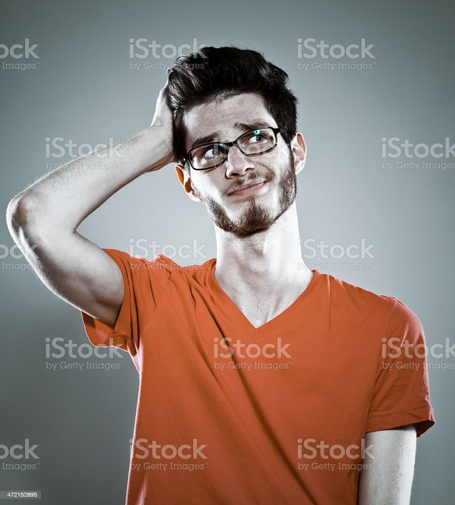 Problem Portrait of young man thinking with hand in hair. Studio shot, grey background. 20-29 Years Stock Photo
