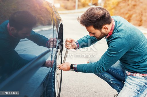 627511482 istock photo Problem with a car. A broken car on the road. Changing wheel 670390636