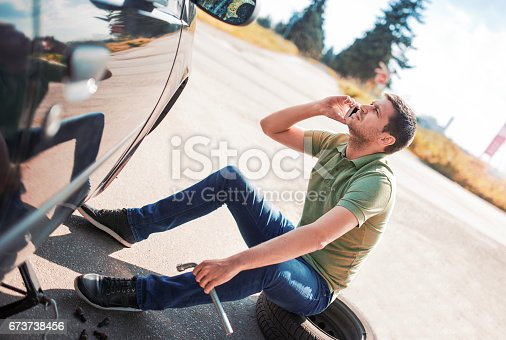 627511482 istock photo Problem with a car. A broken car on the road. Changing wheel 673738456