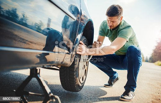 627511482 istock photo Problem with a car. A broken car on the road. Changing wheel 680078882