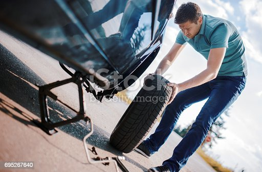 627511482 istock photo Problem with a car. A broken car on the road. Changing wheel 695267640