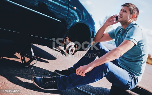 627511482 istock photo Problem with a car. A broken car on the road. Changing wheel 879380422