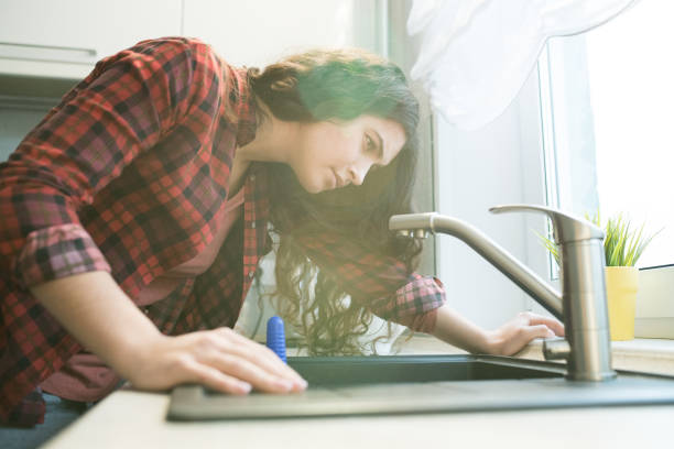 Problem with faucet in kitchen Serious concentrated young woman in checkered shirt checking faucet while having problem with dropping faucet in kitchen leaking stock pictures, royalty-free photos & images