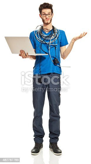 Portrait of worried young man with a lot of cables on his neck, holding a laptop in hand. Studio shot, white background.