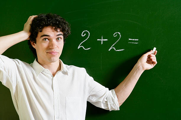 Problem with Maths Student at the blackboard having difficulties in solving a simple sum (2+2). illiteracy stock pictures, royalty-free photos & images
