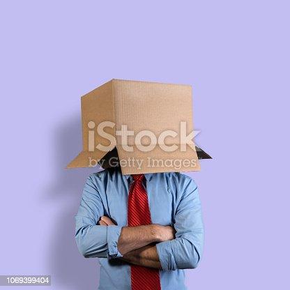 Businessman hiding his head in a cardboard box