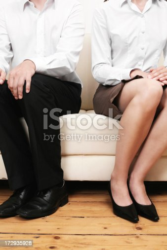 a young couple sitting on a couch having a disagreement. sparse composition, reduced colors.